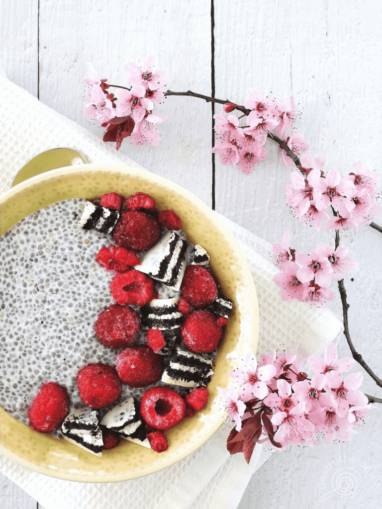 chia puding tavaszi virággal iros bogyós gyümölcsökkel és kekszdarabokkal