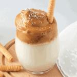 dalgona kávéról készült kép. Átlátszó pohárban alul a tej, felül pedig a habos kávé réteg, kevés kókuszreszelékkel megszórva, rolettivel