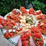 paradicsomos bruschetta pirított baguette szeleteken zöld olajbogyóval, és kék sajttal tálalva